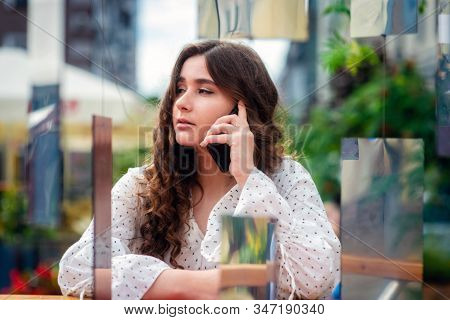 A Young, Sympathetic, Dark-haired Woman Using A Smartphone. Portrait Of A Woman Through A Mirror Ins