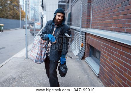 Homeless man with bag on city street