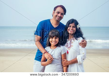 Young Indian Family Relaxing At The Beach On Beautiful Summer Day In Goa