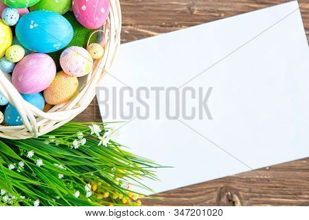 Blank Sheet With Easter Decorations On The Brown Wooden Background. Easter Greeting Card