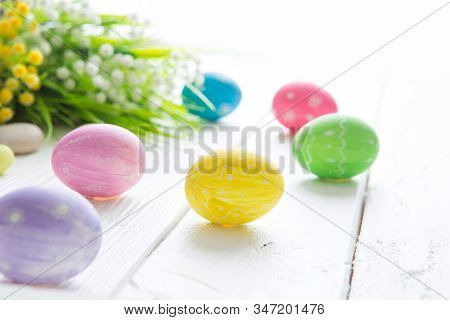 Easter Eggs Flowers Easter Decoration. Colorful Easter Eggs And Flowers On Wooden Table.