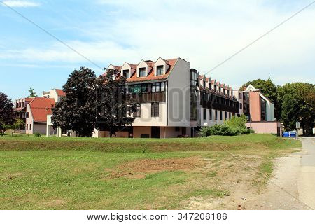 Renovated Retirement Home Or Old Peoples Home Building With Faded Pink Facade And Wooden Window Blin