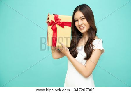 Happy Beautiful Asian Woman Smile With Gold Gift Box Isolated On Light Green Background. Teenage Gir