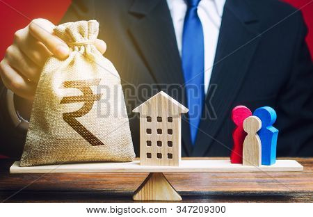 Man Puts Indian Rupee Money Bag And House On Scales With A Family. Assistance With Housing And Finan