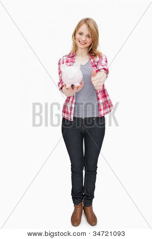 Woman standing while holding a piggy bank against a white background