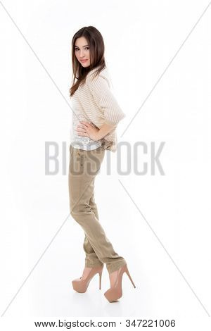 Full lenght portrait of attractive cheerful teen girl looking at camera, isolated on white. Young happy fashion dressed beige trendy clothes