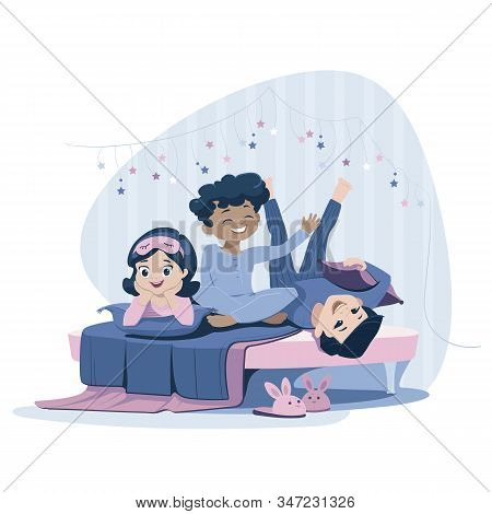 Three Cheerful Kids Of Diverse Race In Blue Nightwear Lie On The Bed, Having Pajama Party. Sleepover
