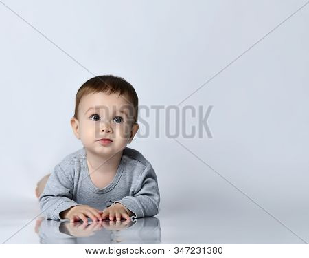 Cute Baby Boy Toddler In Grey Casual Jumpsuit And Barefoot Lying On Floor, Smiling And Looking Up Ov