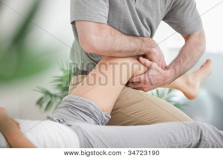Man manipulating the leg of a woman while she is lying in a room