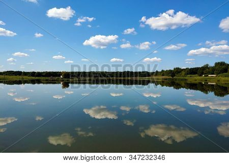 Reflection Of The Sky In Water, A Beautiful Background With Blurry Reflection Of Green Trees And Whi