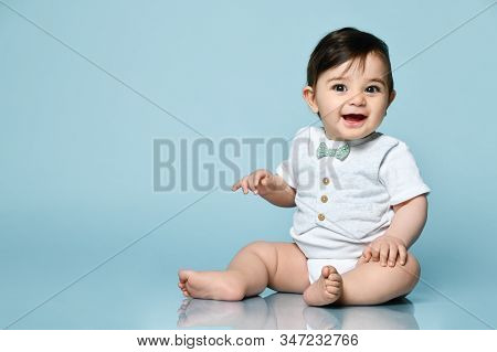 Little Kid In White Bodysuit As Vest With Bow-tie, Barefoot. He Is Smiling, Sitting On Floor Against
