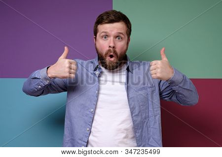 Restrained, Serious Man, Makes An Approving Gesture With Hands, Raises Thumbs Up, Looks In Surprise