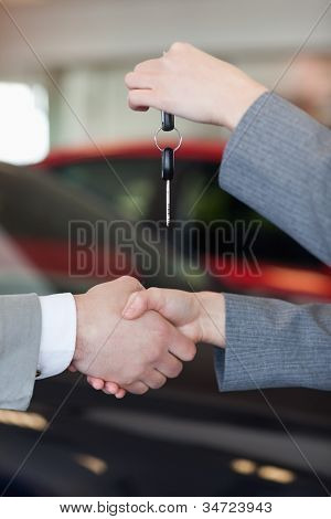 Close up of a woman giving car keys to a man in a dealership