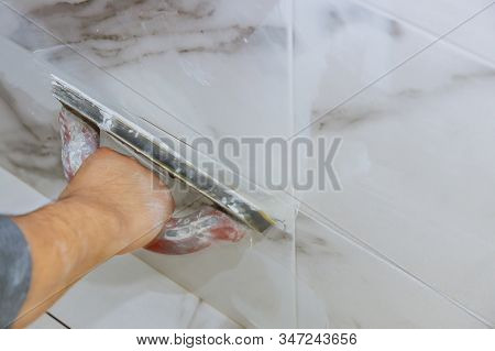 Grouting Ceramic Tiles Process Of Filling The Seams Of Tiled Using A Rubber Trowel