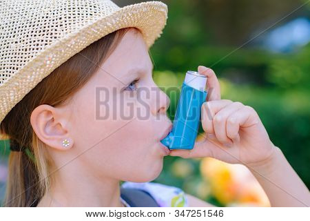 Girl Having Asthma Using Asthma Inhaler For Being Healthy - Shallow Depth Of Field - Focus On Inhale