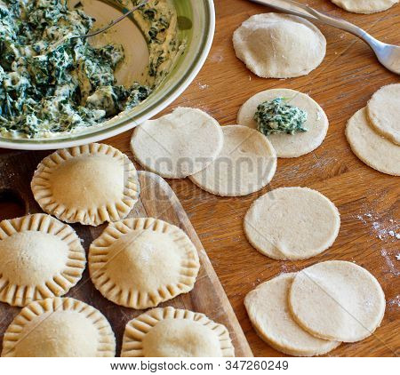 Making Ravioli With Ricotta Cheese And Spinach On A Wooden Board