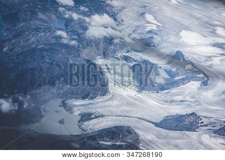 Greenland, Aerial View Of Glacier And Snow Covered Mountains. This Is A Consequence Of The Phenomeno