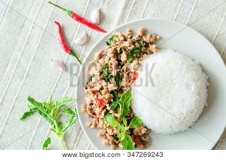 Rice Topped With Stir-fried Pork And Basil In Dish On Tablecloth.
