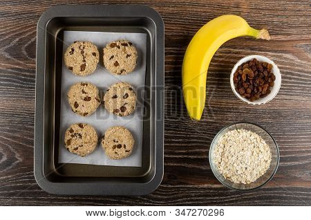 Raw Cookies From Oat Flakes, Banana And Raisin On Oven-tray, Yellow Banana, Bowls With Raisins And O