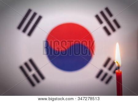 Burning Candle On The Background Of The Flag Of North Korea. The Concept Of Mourning And Sorrow In T