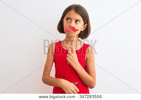 Beautiful child girl holding fanny party mustache standing over isolated white background serious face thinking about question, very confused idea