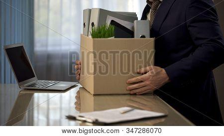 Employee Putting His Stuff From Work Desk In Carton Box, Leaving Job, Retirement