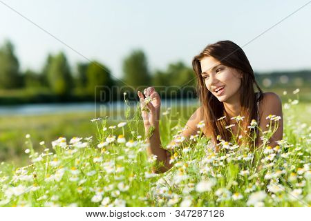Young Sexy Brunette Woman Lying On Grass And Smiling On Summer Day With Green Nature And River At Ba