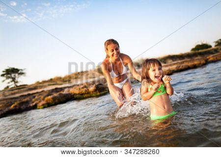 Young Blond Woman In White Bikini And Small Happy Girl Having Fun In Sea Water With Rocky Beach At B