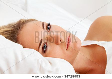 a young woman lies awake in bed. sleepless and thoughtful.