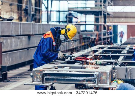 Blue-collar workers at work in a big factory. Heavy industry, labor in shipyard