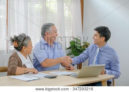 Old Man And Young Man Shake Hands Together After Dealing Some Business About Financial And Healtcare