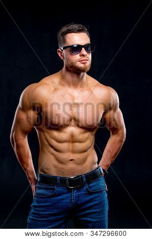 Sexual Muscular Man Posing Over Dark Background. Muscular Body And Strong Abs. Looking At Side. Stud