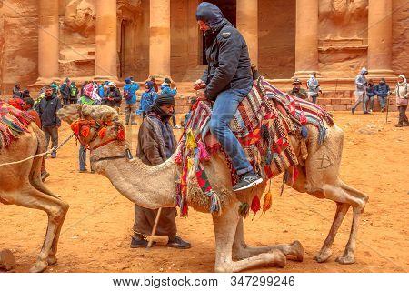 Petra, Jordan - Jan 4, 2020: Close Up Of A Bedouin As He Drops A Tourist From His Dromedary Camel In