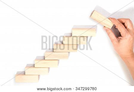 Hand Arranging Wood Block Stacking As Step Stair Isolated On White Background. Business Concept For
