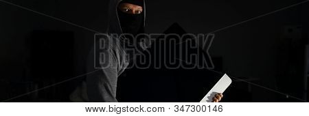 Portrait Of Terrified Thug Holding Electronics Of Popular Company In Hands. Criminal Wearing Black M