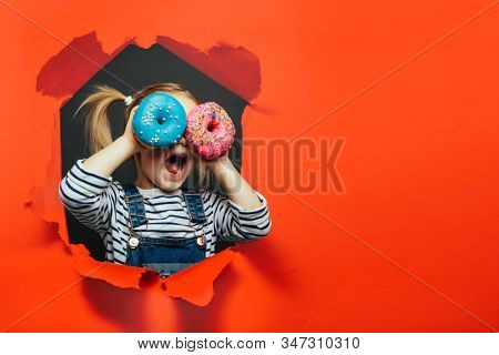 Happy cute boy is having fun played with donuts on Lush Lava background wall. Bright photo of a boy. Colored donuts