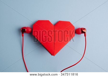 Listen To Your Heart. Red Origami Heart With Headphones On Blue Background. Love Listening To Music