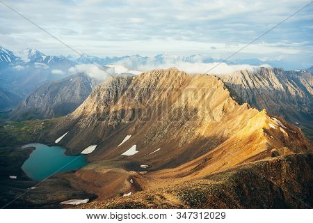 Atmospheric Alpine Landscape To Low Clouds On Big Golden Pointy Rockies In Sunlight. Giant Mountains