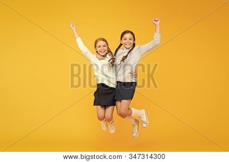 Happy Winners. Little School Girls Jumping And Making Winner Gestures On Yellow Background. Cute Sma