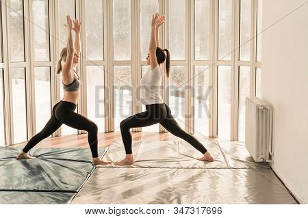 Two Beautiful Girls Practicing Yoga. Warrior Pose. Virabhadrasana. Yoga Concept, Healthy Lifestyle