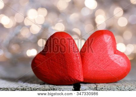 Two red wooden hearts symbol of love on background with beautiful bokeh party lights, Saint Valentine Day celebration
