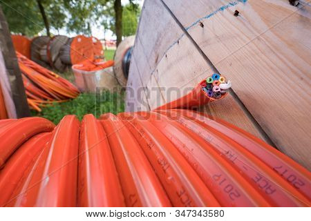 Hengelo, Netherlands - August 25, 2018: Closeup Of A Cable Drum With Orange Fiber Glass Cable On A C