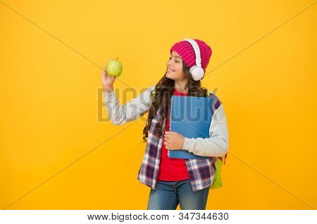 Healthy Eating Habits For Your Child. Happy Girl Hold Apple Yellow Background. Enjoying Healthy Scho