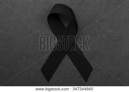 Black Awareness Ribbon On Black Background. Mourning And Melanoma Solidarity Symbol. 3d Rendering