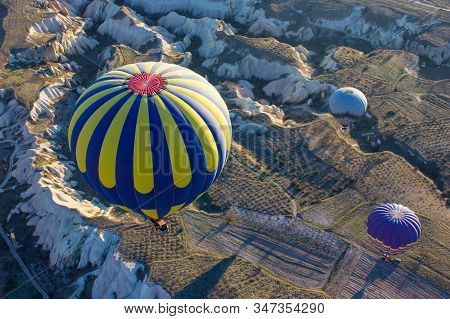 Hot Air Balloons In The Sky During Sunrise. Flying Over Colourful Rock Formations In Cappadocia, Tur