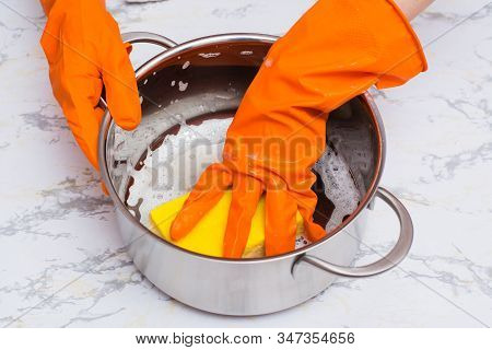 Female Hands Lather The Pan With A Sponge For Washing Dishes On The Table
