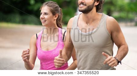 People running in a park, cardio and stamina workout outdoor. Shallow depth of field, focus on the woman