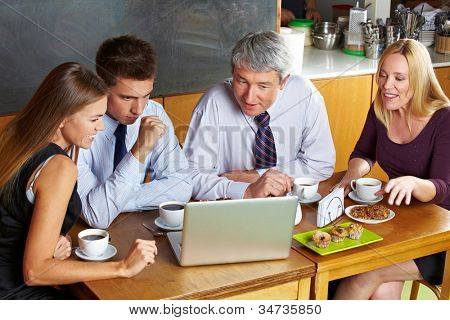 Business people looking at laptop in caf�© during a meeting