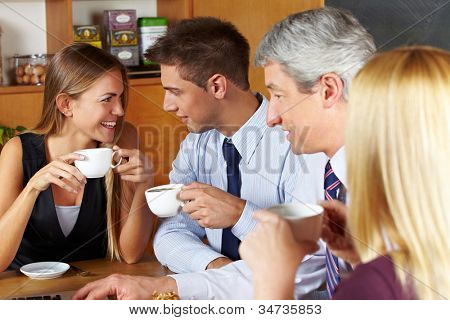 Four smiling business people taking a break with coffee in a caf�©