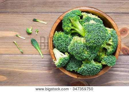 Ready To Eat Fresh Raw Broccoli Is Divided Into Inflorescences In A Wooden Plate On A Wooden Table.